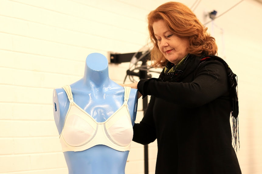 Deirdre McGhee puts a white sports bra on a blue mannequin in a lab.