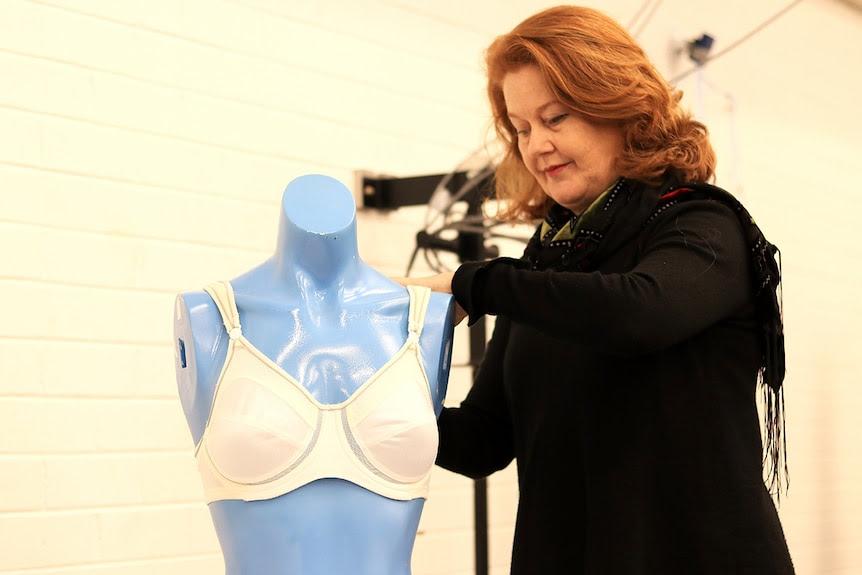 Deirdre McGhee puts a white sports bra on a blue mannequin in a lab.
