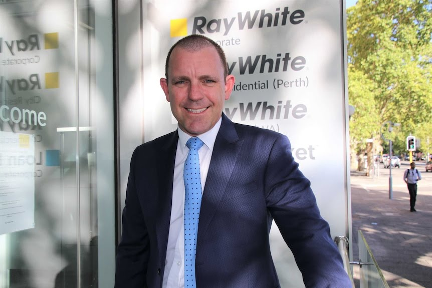 Mark standing in front of a sign with Ray White logo.