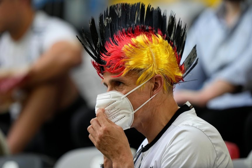 A man with a black, red and yellow mohawk, holds a mask in front of his face