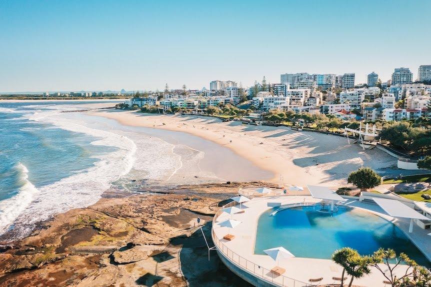 An serial view of a beachside pooland the ocean.