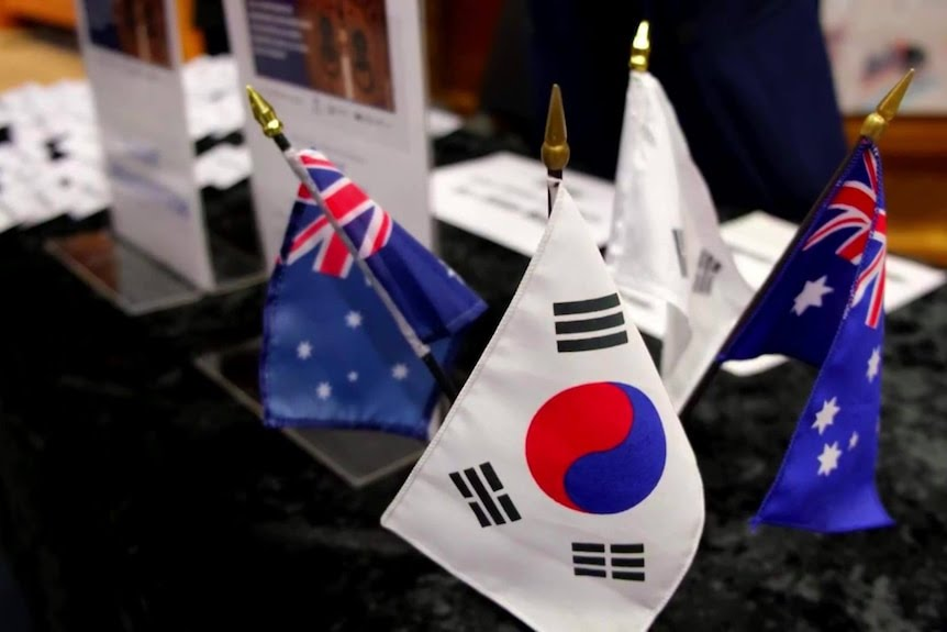 Miniature South Korean and Austalian flags sit on a table