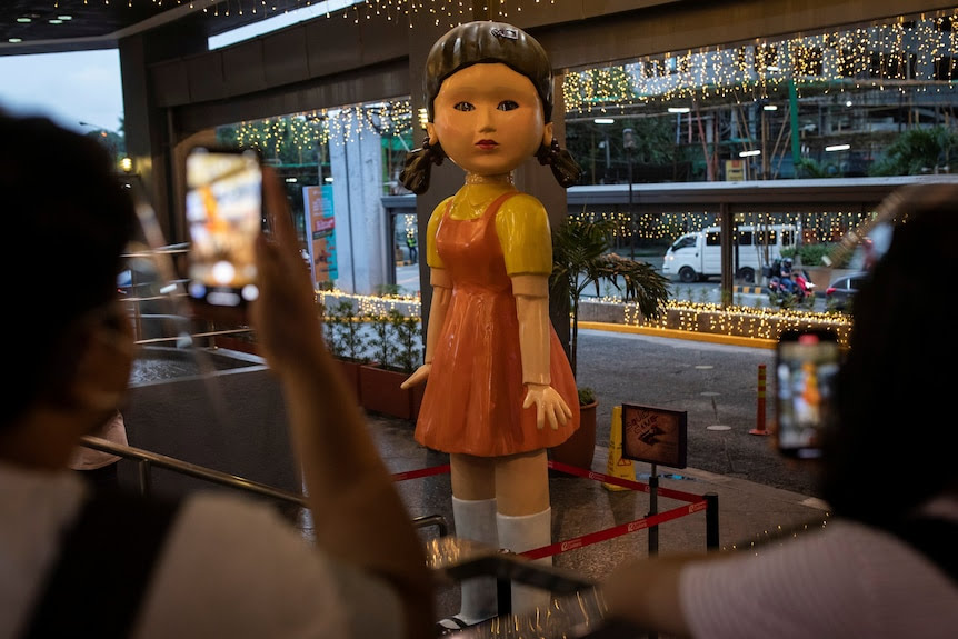 A 3-metre tall doll from the series Squid Game stands in a shopping centre