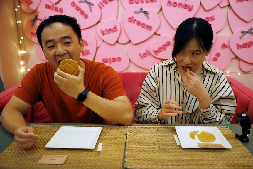 Two people lick honeycomb pieces replicating a game from the series Squid Game