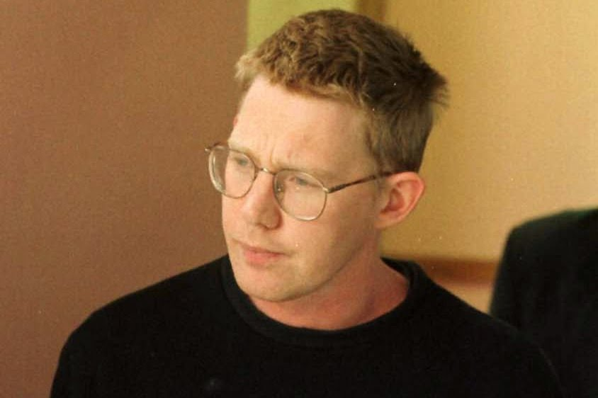 Christopher John Lewis. He is wearing round glasses, he has red hair and a black Quicksilver sweatshirt on.